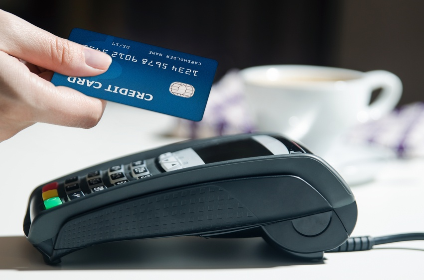 Hand holding a credit card over a payment terminal