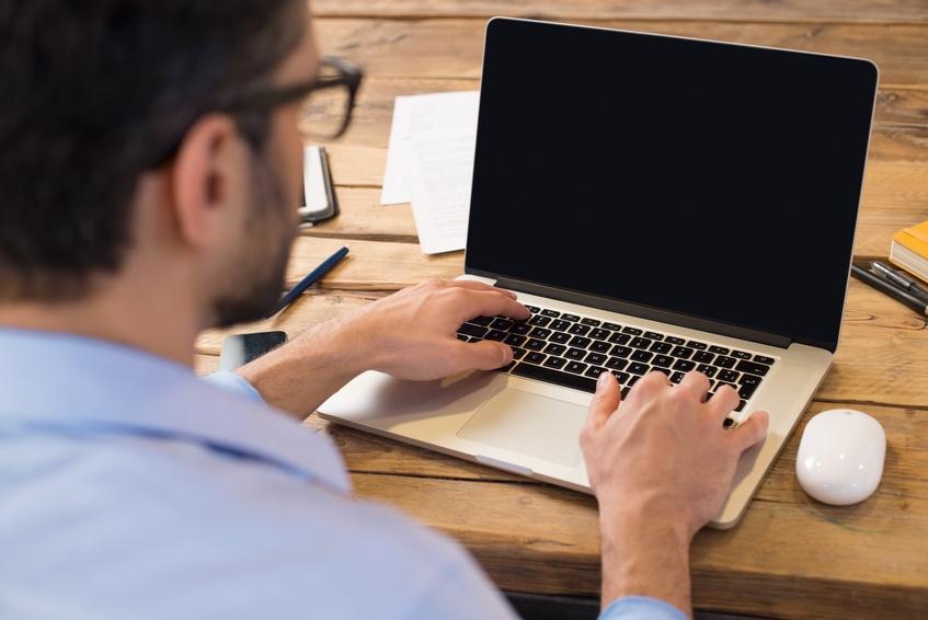 Man typing on laptop keyboard