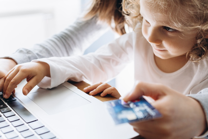 Small child with a guardian making an online purchase